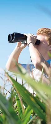 Rothaariger Junge mit Fernglas in Feld